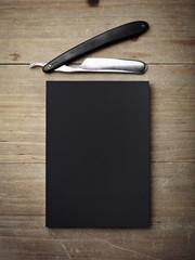 Straight razor and black paper on wood desk