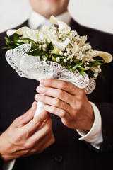 Closeup vertical image of a groom holding wedding spring flowers