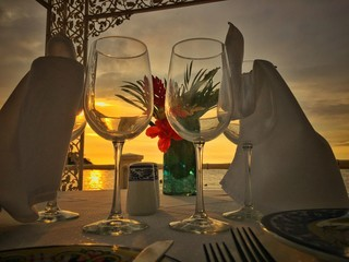 romantic dinner table setup on beach at sunset