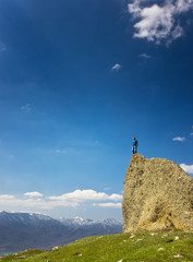 man on the cliff in mountains at above sea