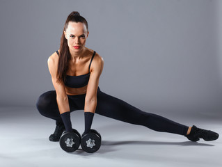 Athletic woman pumping up muscles with dumbbells and stretching