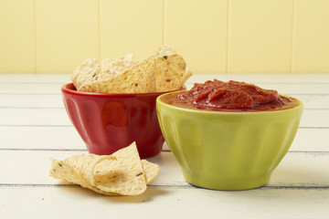 Tomato dip and nachos (corn chips for dipping) on a white table.