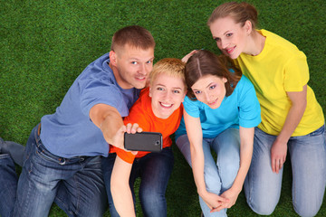 Group of young people sitting on green grass with  phone