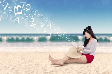 Beautiful woman using tablet at coast