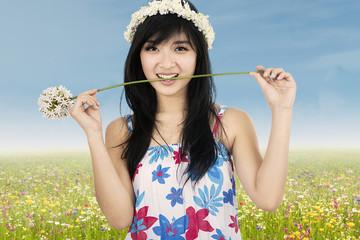 Cute beautiful woman biting flower