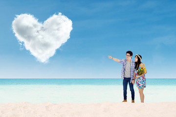 Couple with heart shaped cloud at beach