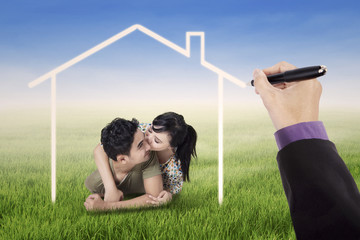 Couple kissing under a dream house