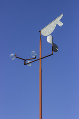 Vintage wind vane on blue sky