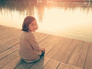 Niña sentada en muelle de lago
