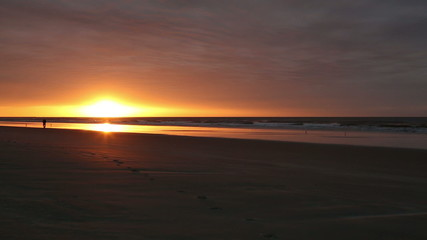 a man walking in the distance along the beach at sunrise