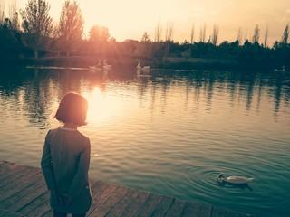 Niña mirando pato en lago