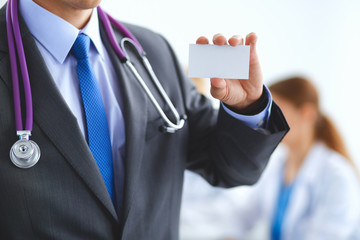 Male doctor holding blank  white card