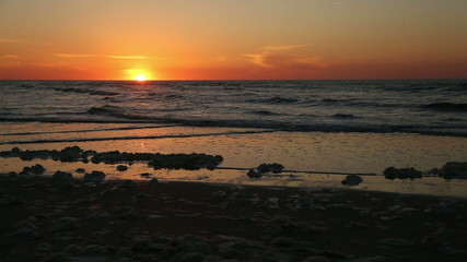 Beach sunrise with sea foam washing up on the beach