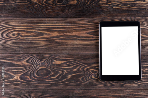 canvas print picture Tablet computer on the old wooden boards. White screen.