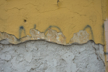 Muro vecchio con graffi e scritte, intonaco danneggiato