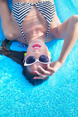 Woman wearing sunglasses in a swimming pool