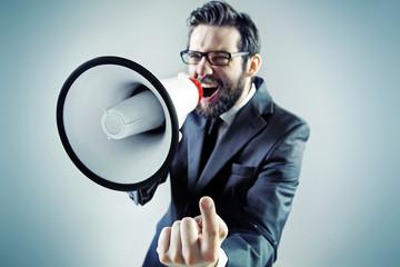 Agressive businessman yelling over the megaphone