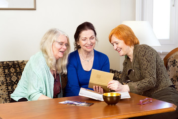 Happy Women Looking at their Old Photo in an Album.