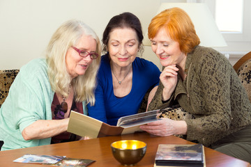 Middle Age Female Friends Looking at Photo Album.