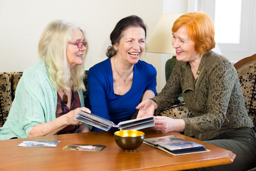 Adult Women Friends Laughing at Old Photos.