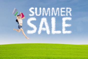 Shopaholic jumps with summer sale sign