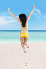 Sexy woman in bikini jumping