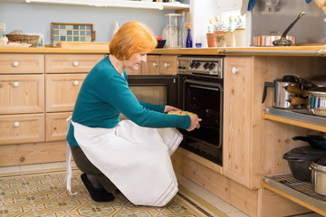 Blond Mom With Apron Putting a Cake in the Oven.