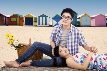 Two young couple picnic at beach