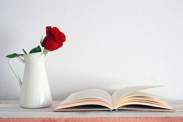 A rose in a vase beside an open book.