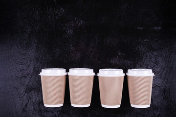 4 paper cups for coffee, tea on a black background.