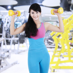 Woman train her biceps at gym center