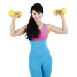 Young fitness trainer with two dumbbells