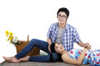 Young couple sitting on mat at studio