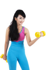 Young woman holding two dumbbells