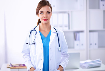 Portrait of young woman doctor with white coat standing in