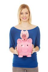 Happy woman holding two piggybanks.