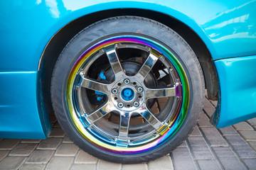 Car wheel on colorful metallic disc, close up photo