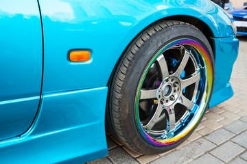 Car wheel on colorful metallic disc, closeup photo