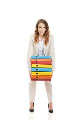 Female carrying heavy binders against.