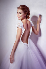 A beautiful woman in wedding dress is standing at a wall half tu
