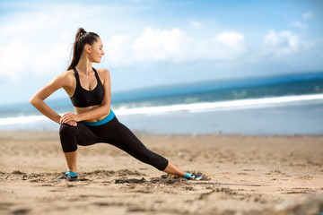 Attractive fit woman stretching  on beach