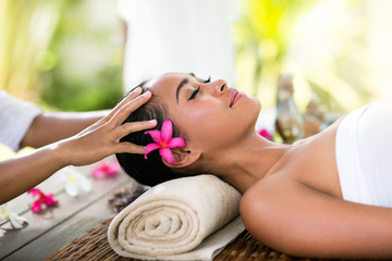 Young woman receiving recreation Balinese massage