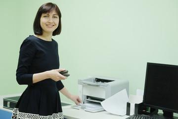 Secretary in office working on printer