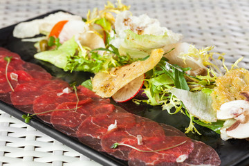 Beef carpaccio with parmesan cheese, capers and rocket salad