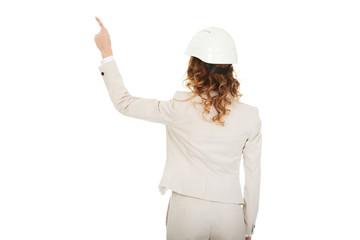 Businesswoman in white helmet pointing up.