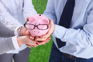Businesswoman and man holding a piggy bank