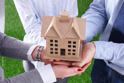 Group of businesspeople holding model house - 81788341