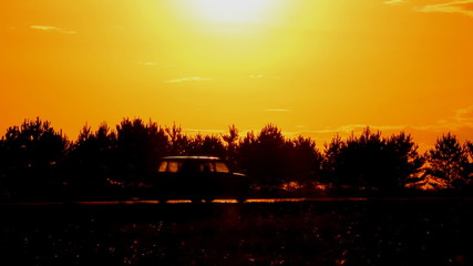 Cars driving on the highway. Sunset against the sun