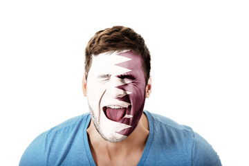 Screaming man with Qatar flag on face.