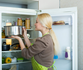 girl looking for something in fridge